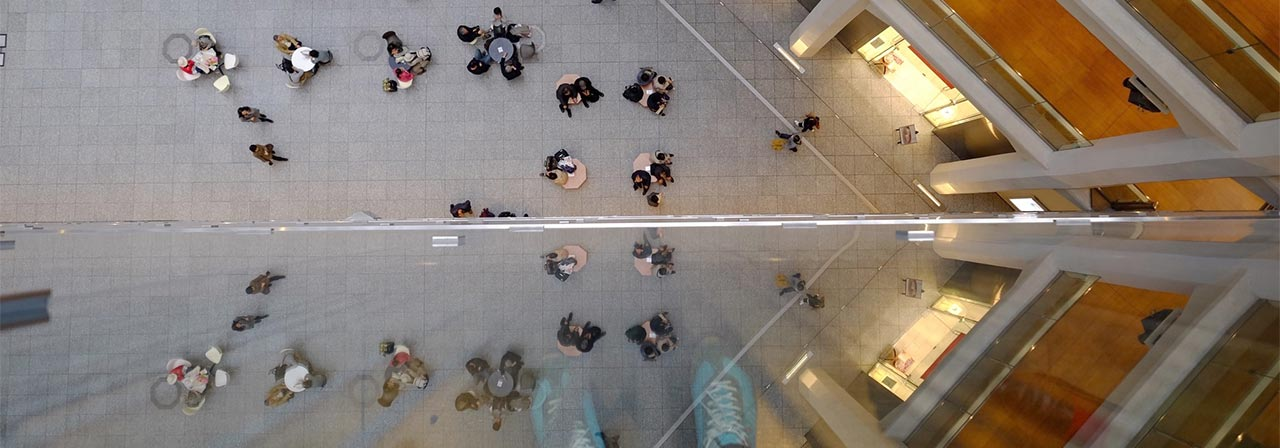 Bird's eye view of building and people sitting around tables